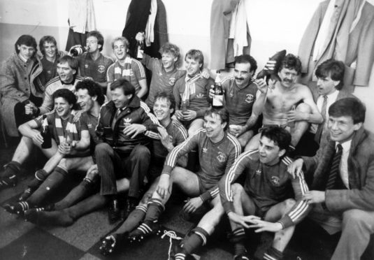 The Aberdeen team toast the taking of the 1984/85 season Premier League title. Back row (l. to r.): Eric Black, Stuart McKimmie, Neil Simpson, Neale Cooper, Ian Porteous, Frank McDougall, Willie Miller, Doug Bell, Peter Weir. Front row (l. to r.): Jim Leighton, Tommy McQueen, Billy Stark, Alex Ferguson, Alex McLeish, Steve Cowan, John Hewitt, Ian Angus.