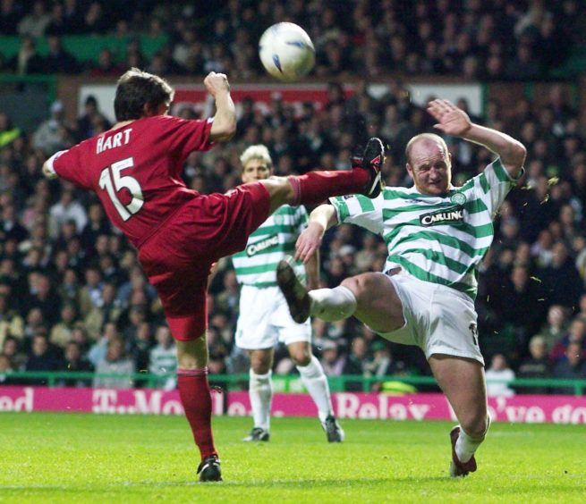 Hartson goes for the ball with Michael Hart of Aberdeen.