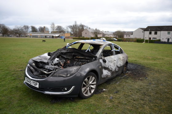 The remains of the vehicle on a field near Cornhill Drive