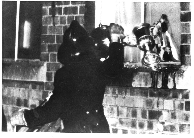The Scottish Cup is passed out of the boardroom into the safe hands of Firemaster John Donnachie when Pittodrie was ablaze in 1971.
