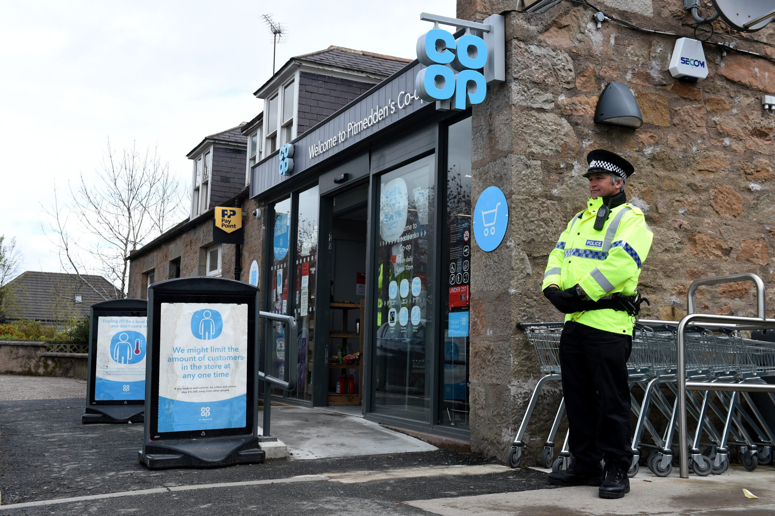 A policeman stands outside the store following the break-in. Picture by Kenny Elrick