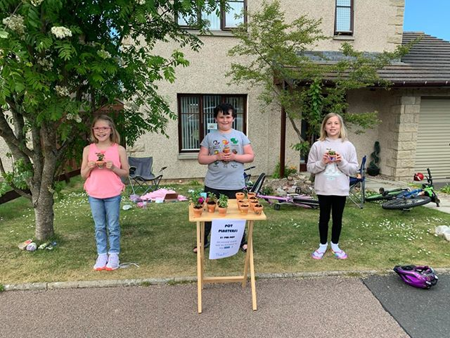Amaia Lawrence, Scott Pert and Analeigha Lawrence selling flowerpots to raise money for the NHS