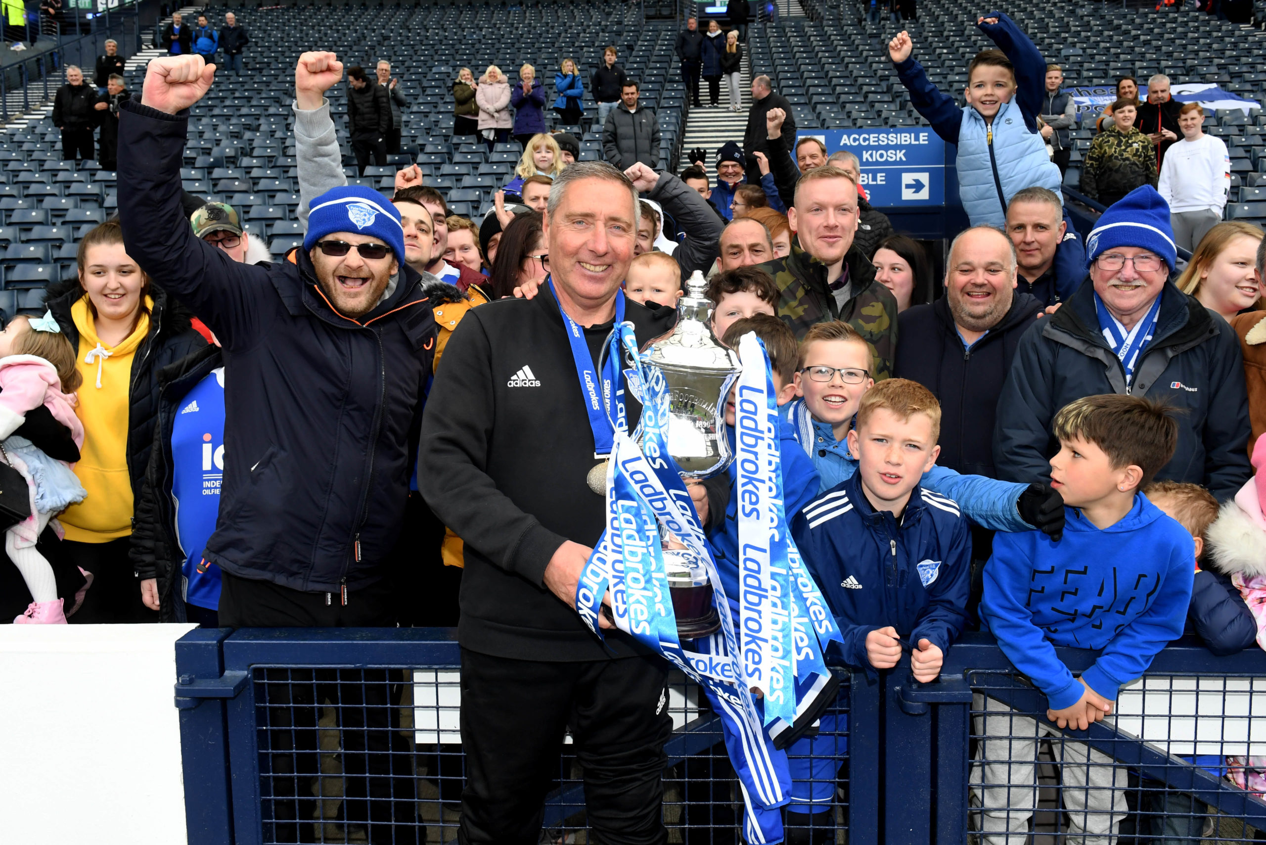 Peterhead manager Jim McInally celebrates with the Ladbrokes League 2 trophy and fans in 2019.