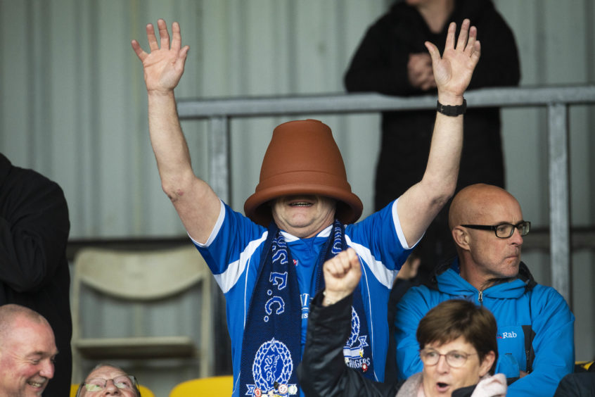 A Cove Rangers fan enjoys the party atmosphere.
