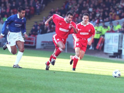 Andreas Mayer tears away from Rangers' Giovanni van Bronckhorst, with Eoin Jess in pursuit.