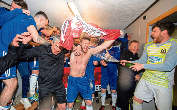 Cove's players celebrates in the away dressing room at Berwick.