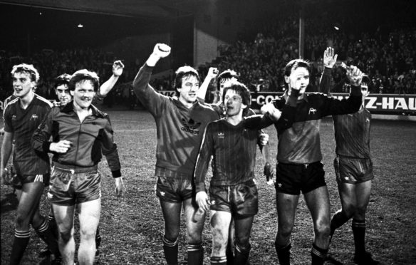 Saluting the fans after dumping Bayern Munich out of the Cup Winners' Cup are (left to right) Neale Cooper, John Hewitt, John McMaster, Neil Simpson, Gordon Strachan, Peter Weir, Jim Leighton and Mark McGhee.