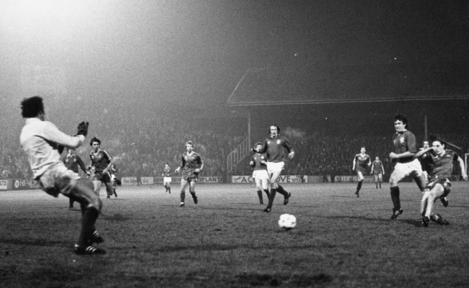 The goal that mattered ... Derek Hamilton guides his shot wide of Peter McCloy, with Sandy Jardine (right) and Colin Jackson floundering in the rear.