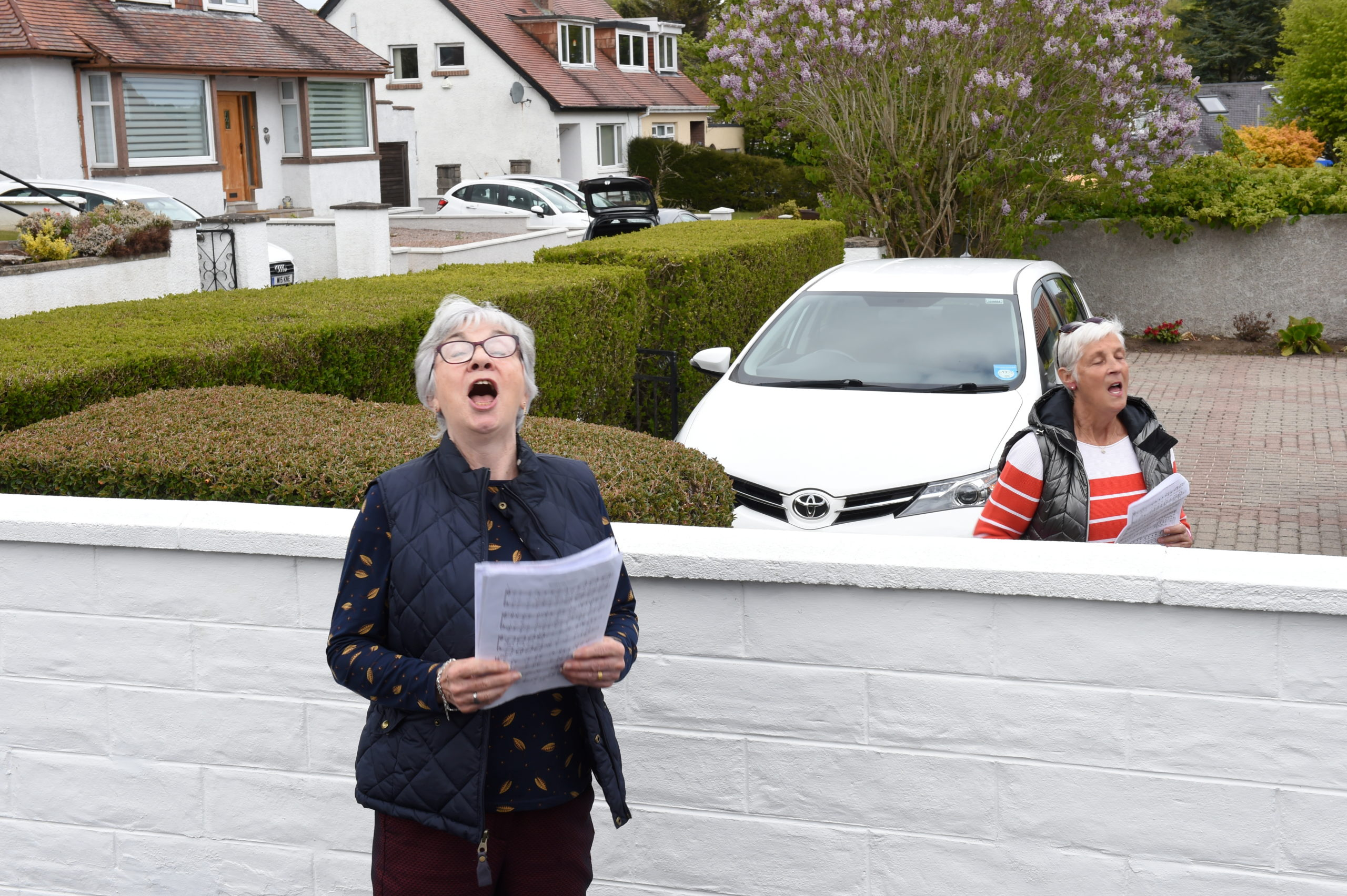 Cults neighbours Carolyn Hodsden and Christine Whitfield who sing four part harmony with the group B Natural practice together over the front garden wall as the group cannot meet due to Covid-19 restrictions