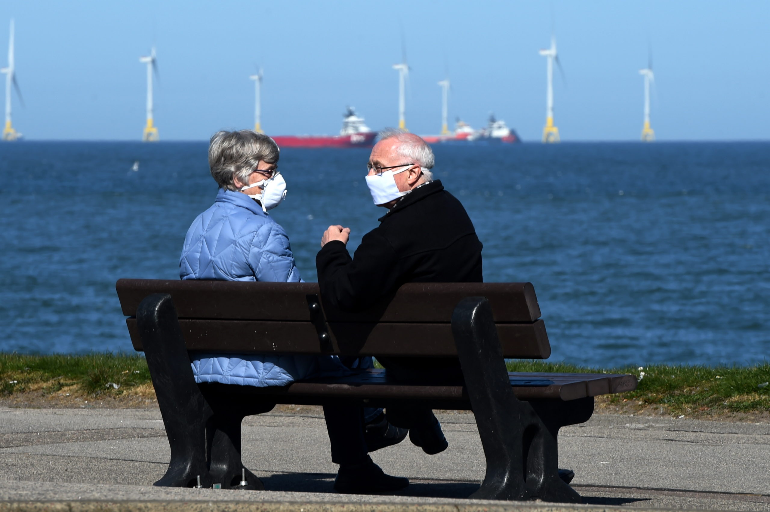 A couple relaxing on a bench at Aberdeen Beach with face masks on