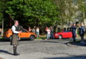 Piper Chris Sibbald performs while people watch