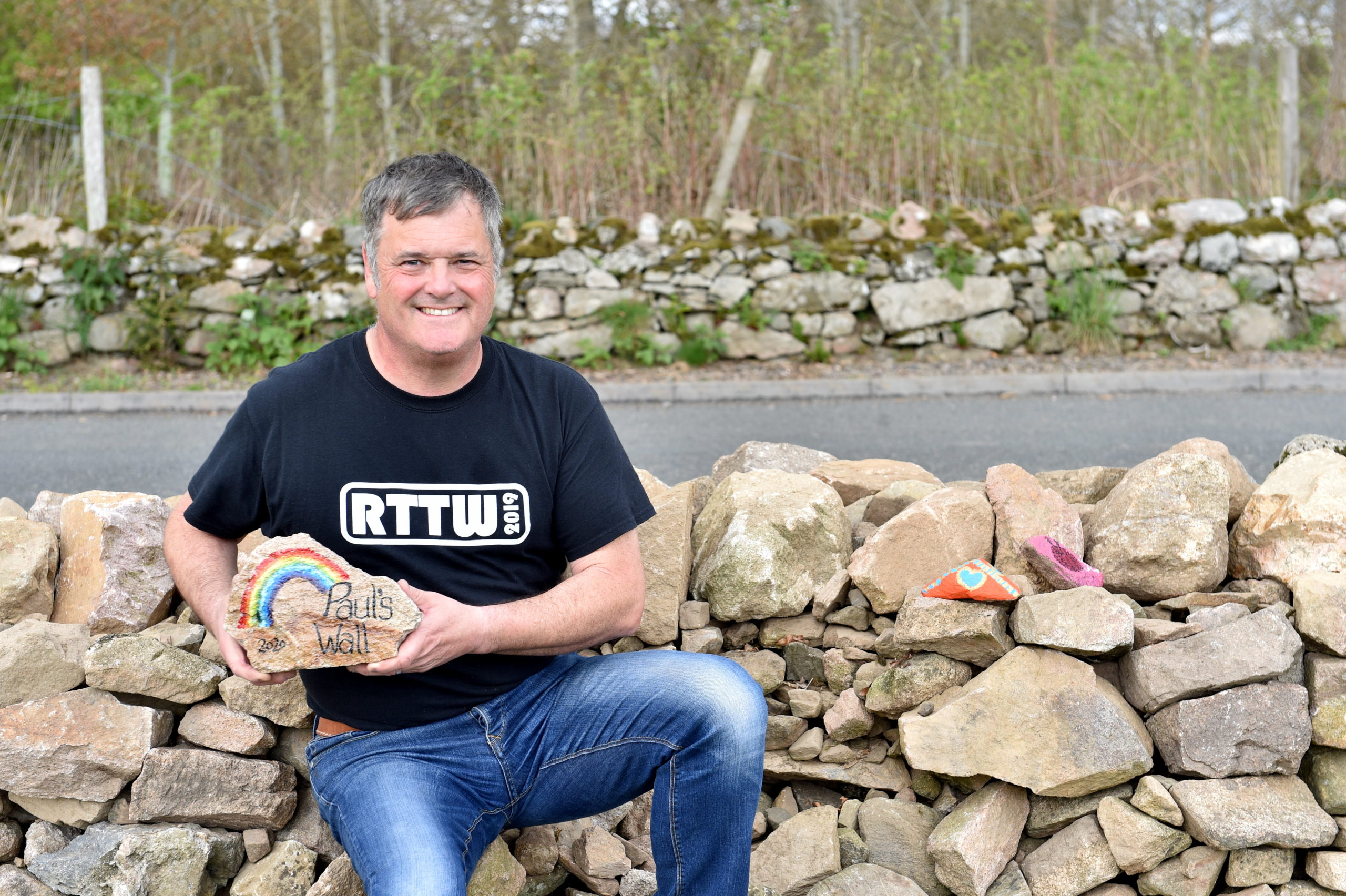 Paul Bailey spent his time on furlough repairing a wall in Udny Green and has had children and locals paint stones to put in it