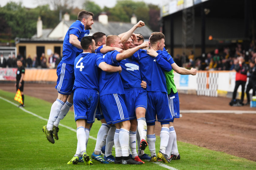 Jordon Brown is mobbed by team-mates.