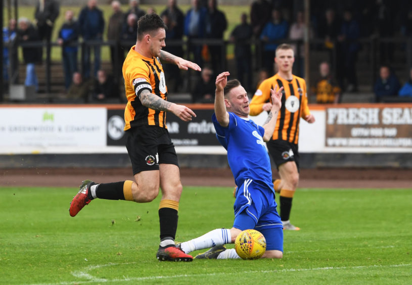 Berwick's Ross Brown (L) challenges Cove's Mitchel Megginson on the edge of the box which results in a red card.