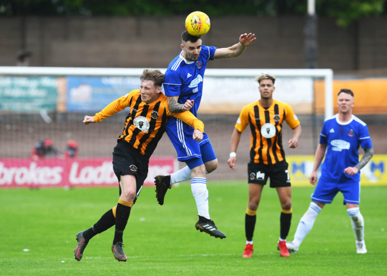 Berwick's Grant Rose is beaten to the ball by Cove's Scott Ross.