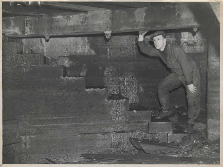 A man stands at the bottom of newly discovered steps at the foot of Market Street, Aberdeen. The steps probably led to the old fish market which was on the site of the present labour exchange.  8 November 1946.