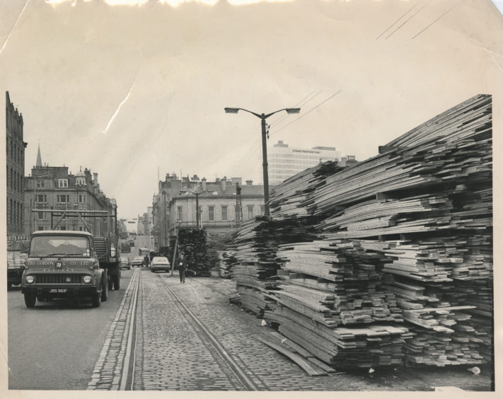 Aberdeen harbour, in 1969, was one of the few open harbours in the UK and was a popular walk for many visitors, and locals alike.  Here pedestrians negotiate huge piles of imported timber lining the harbour on South Market Street.   7 March 1969.