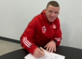 Jonny Hayes putting pen to paper on his Aberdeen deal.