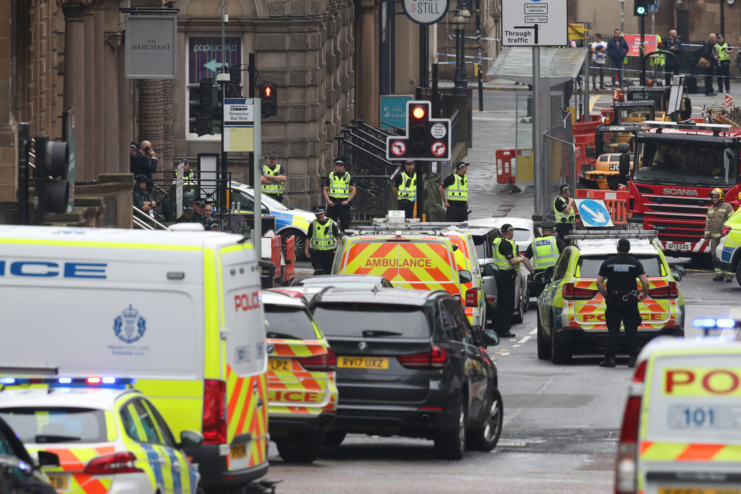 A heavy police presence at the scene in West George Street, Glasgow, where a man has been shot by an armed officer after another police officer was injured during an attack.