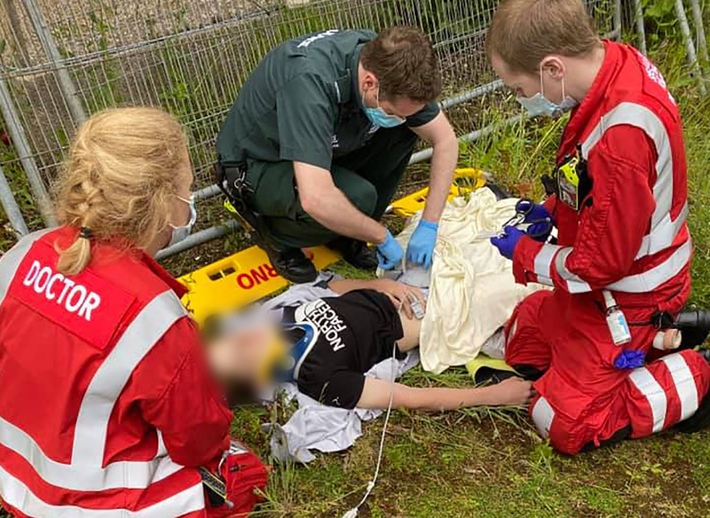 Paramedics treat Logan at the scene after he fell from a derelict building