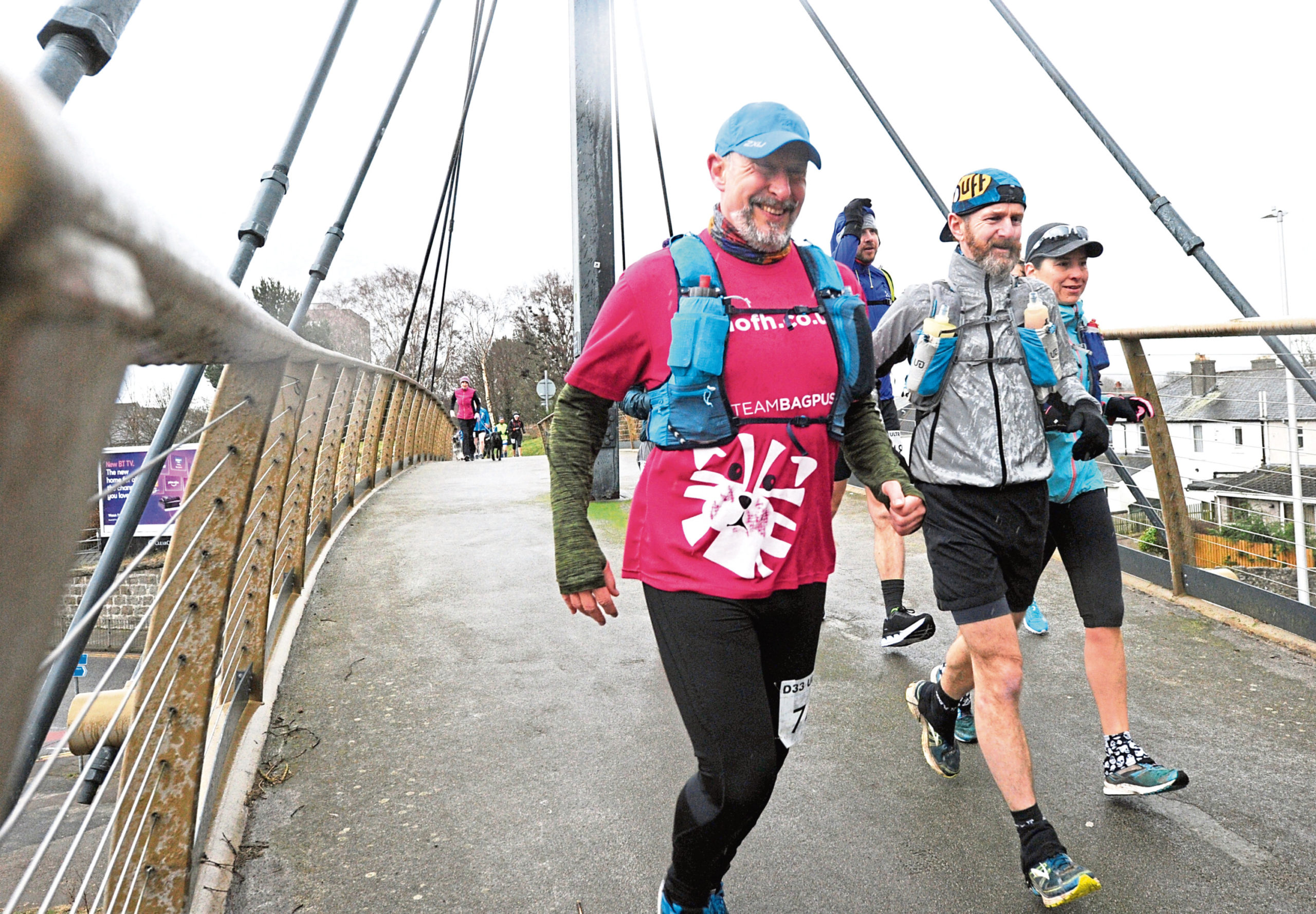 This year's Dee 33 mile ultra-race started at the Duthie Park. Runners go over the Holburn footbridge near the start of the race as the rain falls. Picture by COLIN RENNIE
