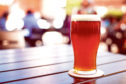 Pint of crafted ale on wooden table in beer garden; Shutterstock ID 338385629; Purchase Order: -