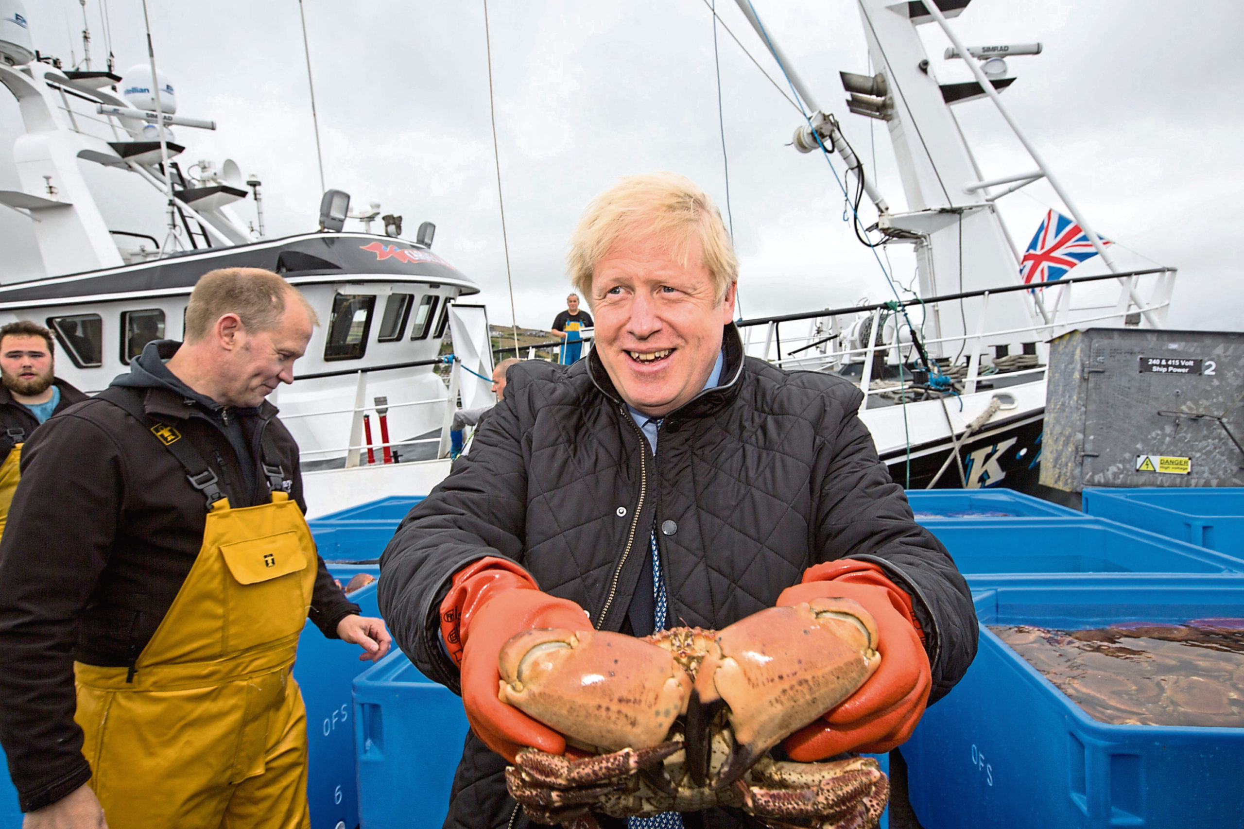 Prime Minister Boris Johnson holds crabs caught on the Carvela with Karl Adamson at Stromness Harbour