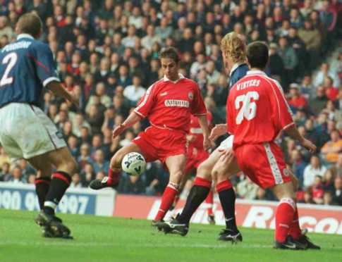Mark Perry puts Aberdeen into the lead against Rangers at Ibrox.