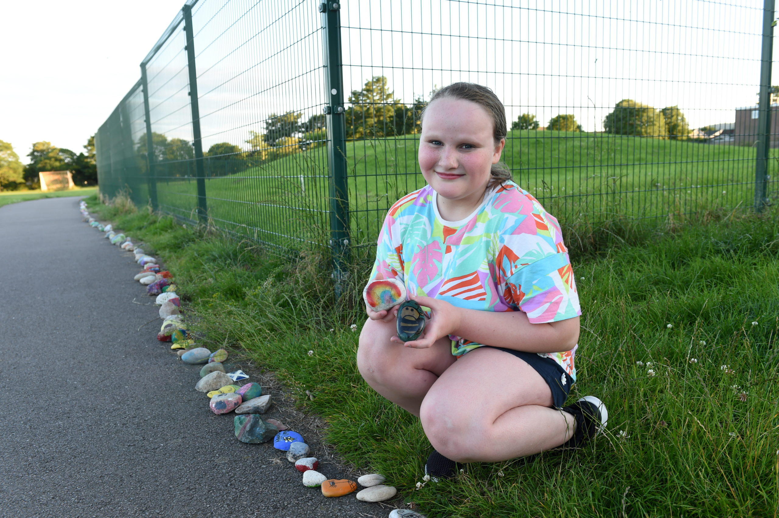 Abbie Colville, 10, adding some rocks to the Dyce Covid-19 snake