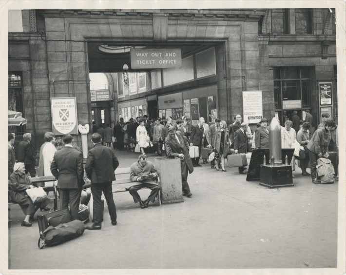 1968: Queues of travellers line up at Aberdeen Joint Station to get away.  People can be seen resting on benches on the concourse as well as standing in line.