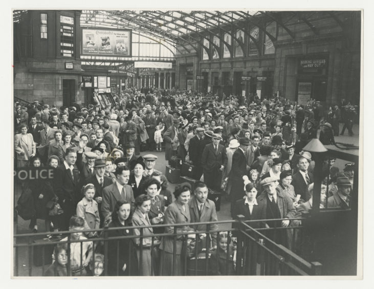 1950: Aberdonians queuing up at Aberdeen Joint Station during the July trades holiday in 1950. The covered concourse is packed with families waiting to get away.