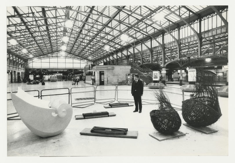 1988: ScotRail manager Nigel Wunsch cast an appraising eye over an exhibition of Scottish sculptures at Aberdeen Station. Organised by the Scottish Sculpture Trust and subsidised by the Scottish Arts Council the show comprises three pieces: from left, Fluted Wave by Sybille van Helem; Orkney Trine by Frances Pelly; and Tree Pods by Valerie Pragnell.