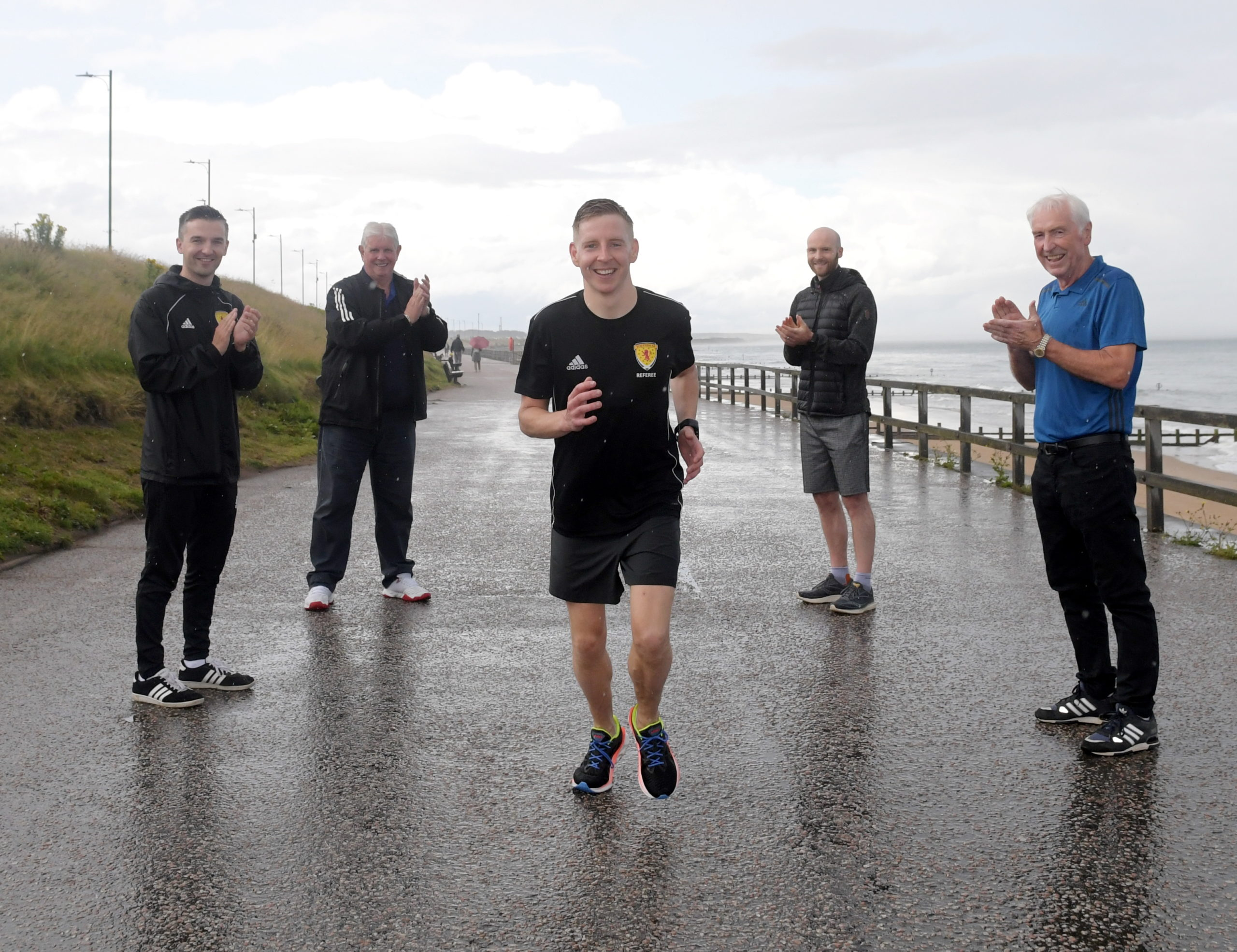 Calum Spence (centre) completes the referees' 24-hour charity running challenge with, from left, Dan McFarlane, Mike Pocock, Paul McAvinue and Sandy Roy. Picture by Kath Flannery