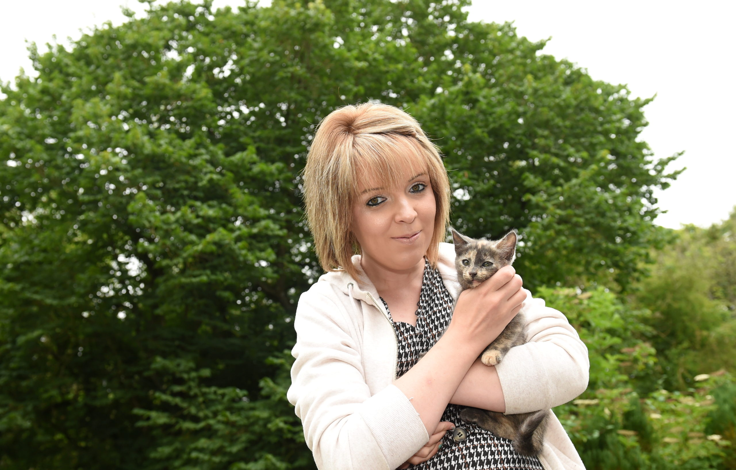Alana Findlay with Aurora in front of the tree where the 14-week-old kitten was stuck. Picture by Paul Glendell