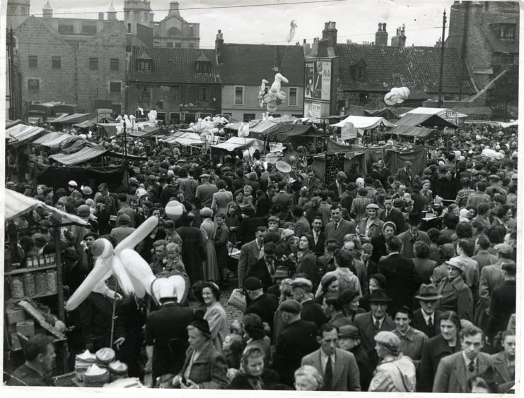 1953: A busy scene of people and stalls at the Timmer Market, Aberdeen.