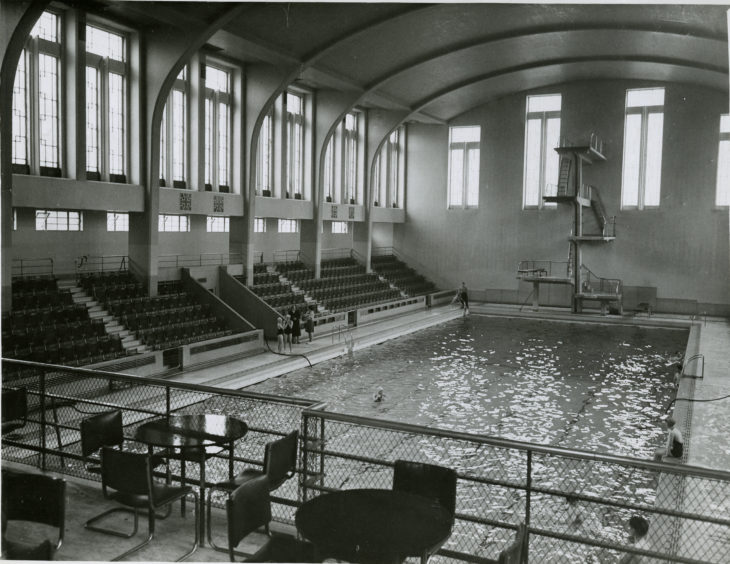 1955: A view of the interior of the Bon Accord swimming baths in Aberdeen looking towards the diving board. Seating areas are visible.