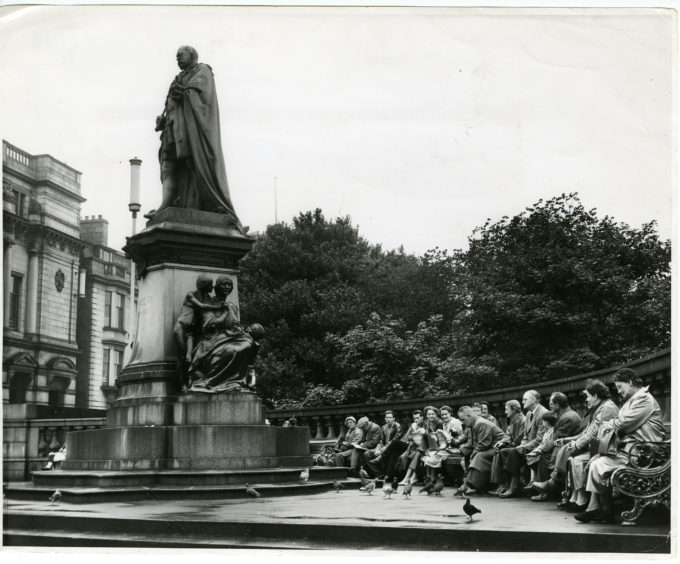 1957: People feed the pidgeons in front of the statue of King Edward VII on Union Street, Aberdeen, at the juntion with Union Terrace.