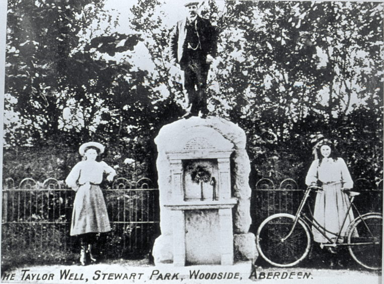 Postcard showing the ornate granite fountain installed in 1906. It is in memory of Jean Taylor who, in 1891, bequeathed £500 for the creation of a playpark in Woodside. The fountain was based on a cast held in the Art Gallery's collection and was sculpted by Arthur Taylor of Jute Street.