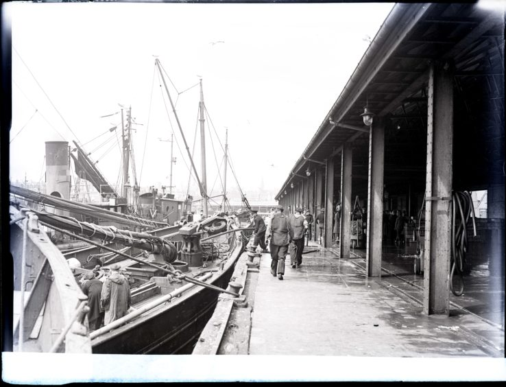 1954: Fishing boats with crews are moored in the dock alongside the Aberdeen Fishmarket.