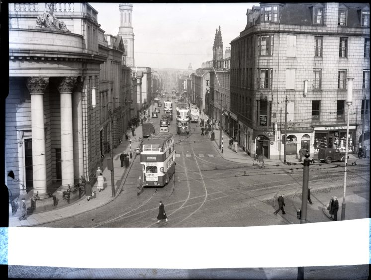 1954: Looking north up King Street from the junction with Castle Street, Aberdeen.  The North of Scotland Bank with its pillars can be seen on the left.  Pedestrians, trams and cars can be seen in the bustling street scene.