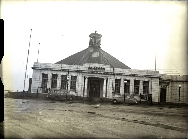 1958: The entrance to the Aberdeen Beach Ballroom with two cars parked in front.