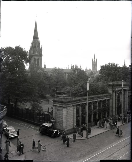 1957: The Union Street, Aberdeen, entrance to St Nicholas' Church and church yard.  Union Street is busy with shoppers and cars can be seen in Back Wynd.  the tower of Marischal College can be seen in the distance.
