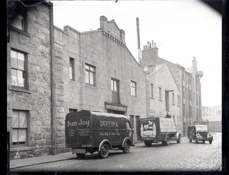 1958: The exterior of Roberton Fruit Products Ltd's factory on Clarence Street, Aberdeen.  Outside are parked there delivery vans for Sun Joy and Dextora aerated drinks.