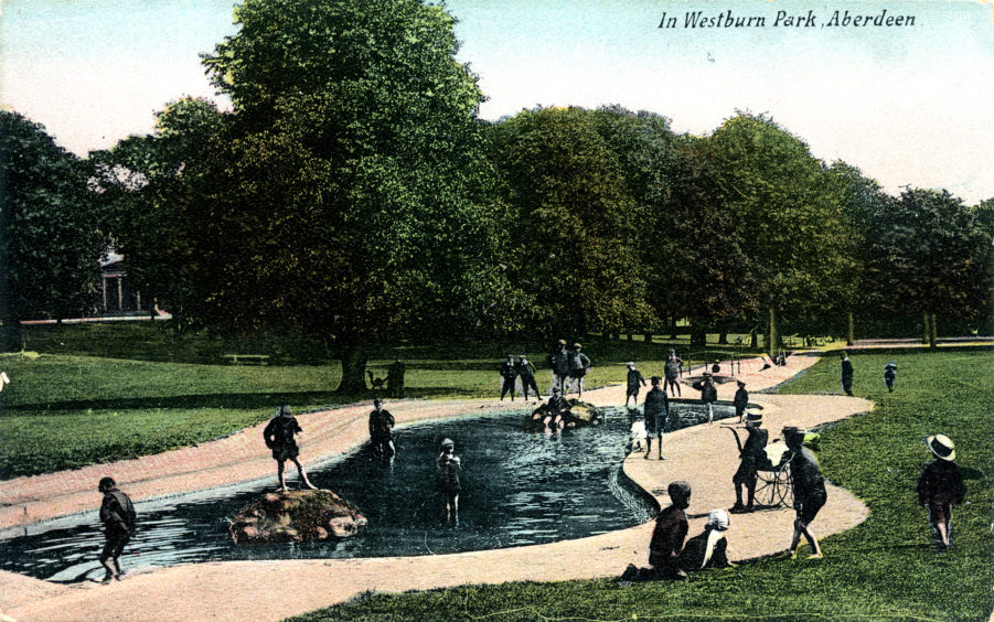 An early 20th century colourised postcard showing children playing in the park's man-made pond. The water is a channelled, open section of the Gilcomston Burn. Aberdeen Town Council created the public park after acquiring the 25-acre estate in 1900.