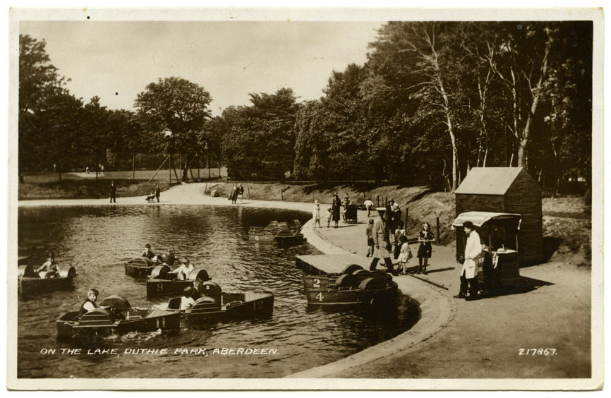 Another postcard from the same period showing pedalos on Duthie Park's Upper Lake. Families, the pedalo attendant and an ice-cream seller stand by the waterside.