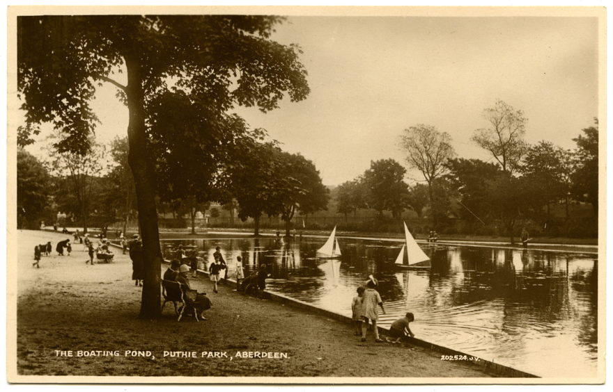 An early to mid-20th century postcard showing yachting on the Lower Lake of Duthie Park. Looking south east, large model sail boats are on the water as families play nearby. This rectangular lake was created in the 1920s.