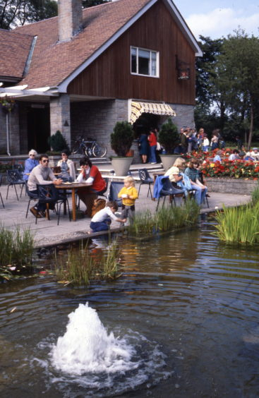 1970s photograph of the park's café with its outdoor seating area and pond. This new café was officially opened by Lord Provost George Stephen in June 1960 during a Town Council tour of city parks.
