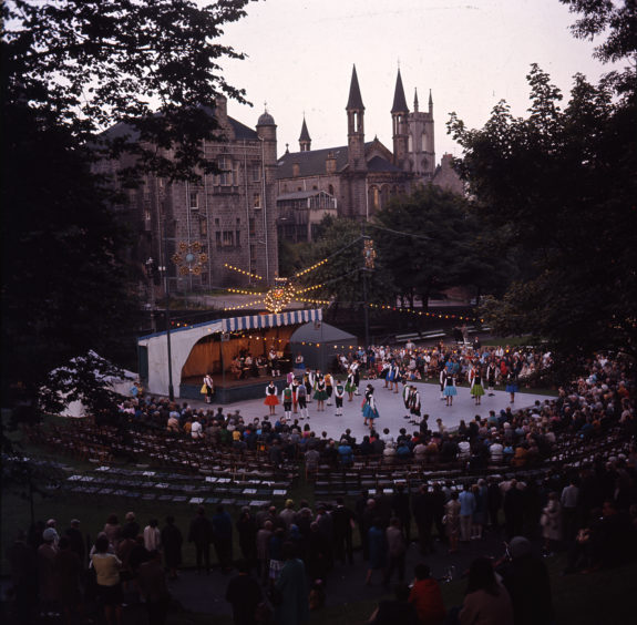 Over the years UTG has played host to a wide variety of entertainment and festivals. This image shows a well-attended evening performance of country dancing during the late 1970s. The Belmont Cinema and Belmont Congregational Church are visible in the background.