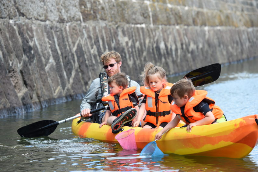 The Bottomley  family  'crabbing' from their canoe in Stonehaven harbour
