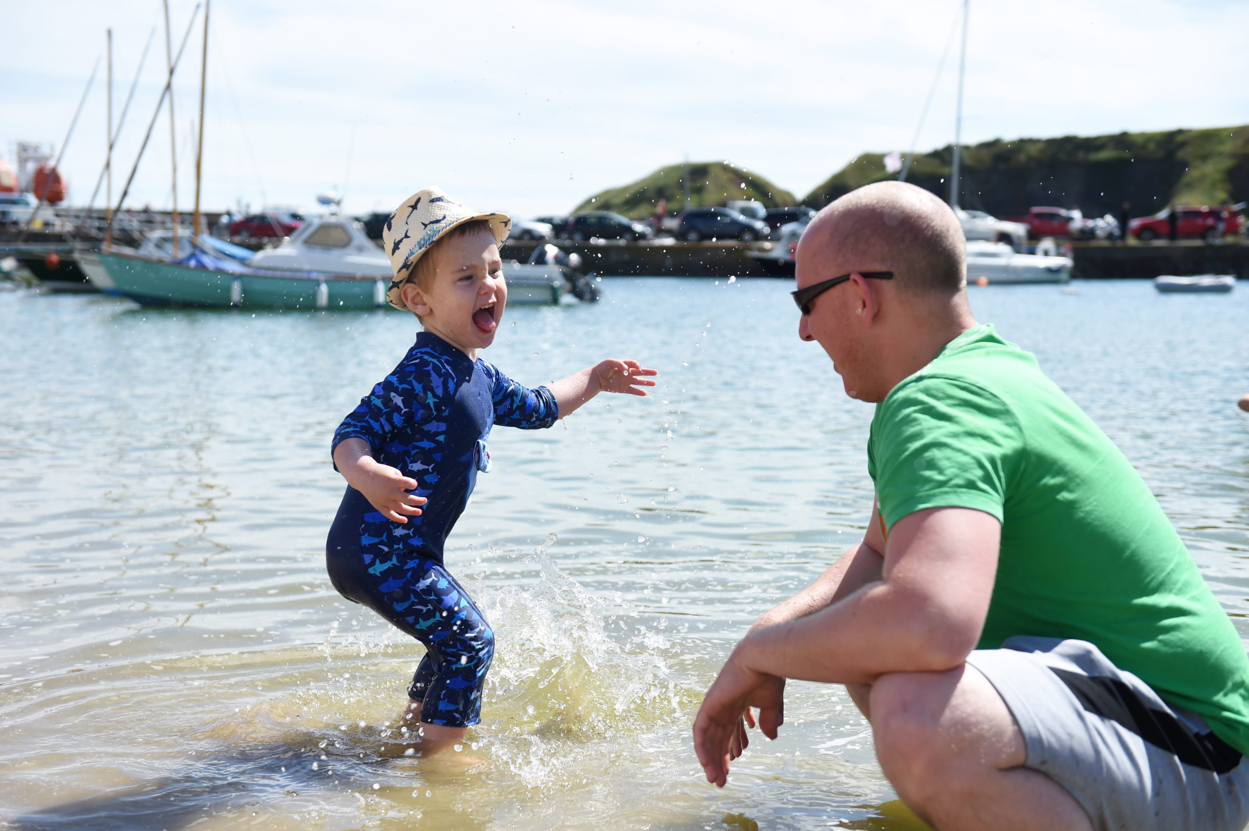 Orion Young, 3, and his father Mike playing in the sea in Stonehaven Harbour Picture by Paul Glendell